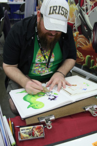 Artist Nate Lovett sketches in front of fans at his booth at Baltimore Comic Con. Photo by Josephine Valois.