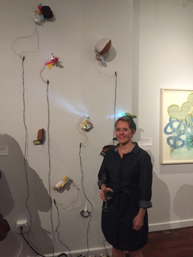 "Bonnie Crawford Kotula stands next to her exhibit titled ""Light Emitting Studies."" Photo by Neil Kenworthy."