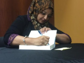 """Rabia Chaudry, an attorney and president of the Safe Nation Collaborative and the co-host of the popular podcasts """"Undisclosed,"""" signs books during an event at Towson University. Photo by  Nick Ferrara."""