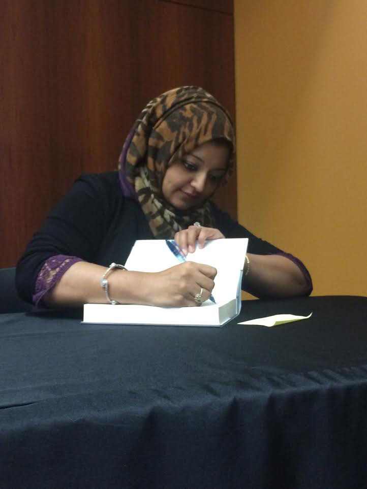 "Rabia Chaudry, an attorney and president of the Safe Nation Collaborative and the co-host of the popular podcasts ""Undisclosed,"" signs books during an event at Towson University. Photo by Nick Ferrara."