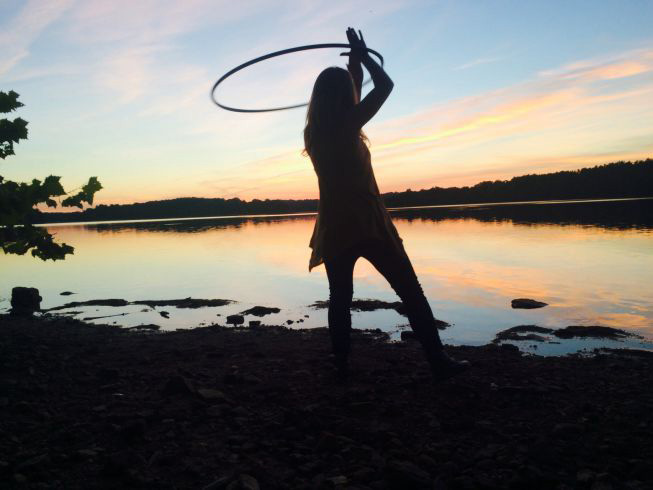 An avid hula hooper spins her hoop while catching a nice view of the sunset.