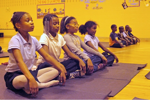 Students practice breathing exercises and yoga as part of the Mindful Moments Program. Photo courtesy of The Holistic Life Foundation.