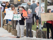 """Matt Crenson (with the """"tree-gate"""" sign) was one of the 50 people who protested Saturday's removal of 30 trees from the proposed Royal Farms gas station in West Towson. Photo by Nick Rynes."""