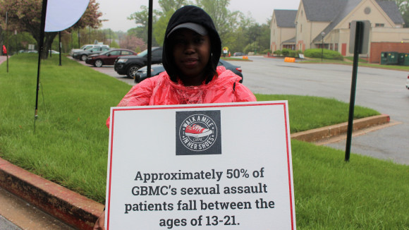 Latoya Yang, a GBMC rehab center worker, as she holds a sign to inform walk participants. Photo by Taylor Nappi.
