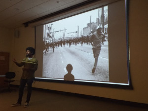 Devin Allen shows a Towson audience some of the photos he took during the 2015 Baltimore uprising. Photo by Billy Owens.